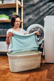 Mulher tirando a roupa na máquina de secar roupa
