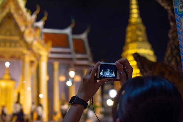 Mulher tirando foto da tailândia à noite e o céu escuro.