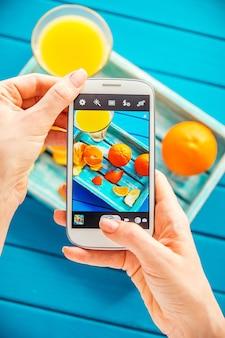 Mulher tirando foto de bandeja vintage com frutas em seu smartphone. vista do topo