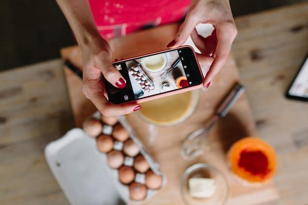 Mulher tirando foto de cozinhar