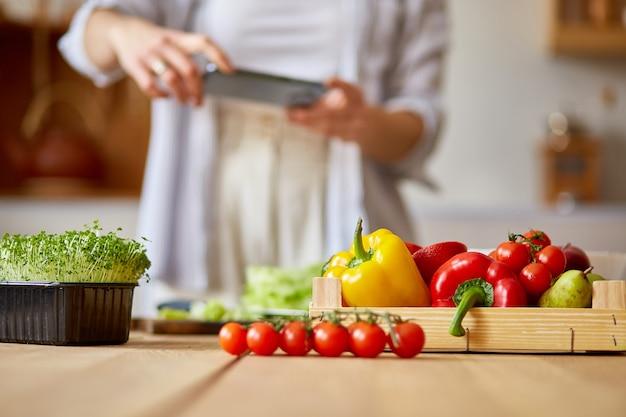 Mulher tirando foto de salada saudável com smartphone para seu blog na cozinha em casa