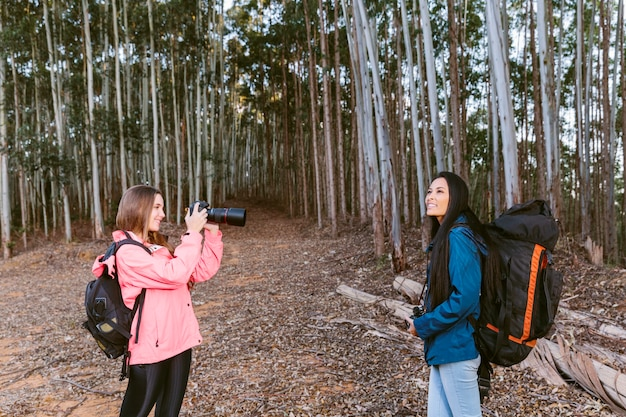 Mulher tirando foto de sua amiga na floresta