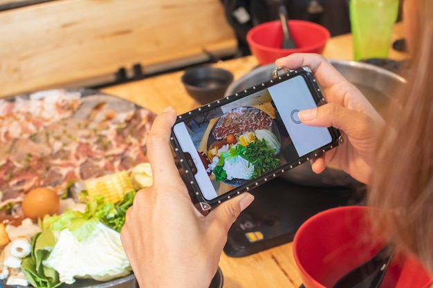 Mulher tirando foto de sukiyaki shabu shabu com smartphone móvel