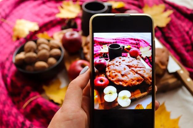 Mulher tirando foto de torta de maçã no celular. atmosfera de outono. foco seletivo