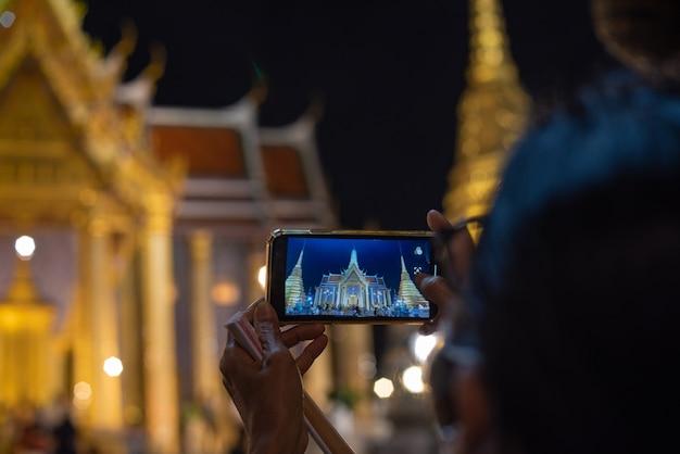 Mulher tirando foto do templo da tailândia com telefone inteligente à noite e o céu escuro.