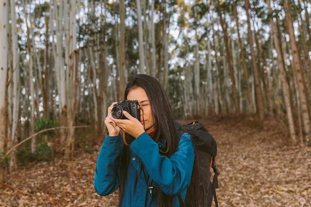 Mulher tirando foto na floresta com câmera