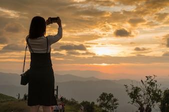 Mulher tirando foto no pôr do sol.
