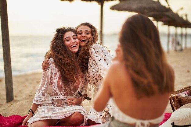 Mulher tirando foto para os amigos em uma toalha vermelha na praia