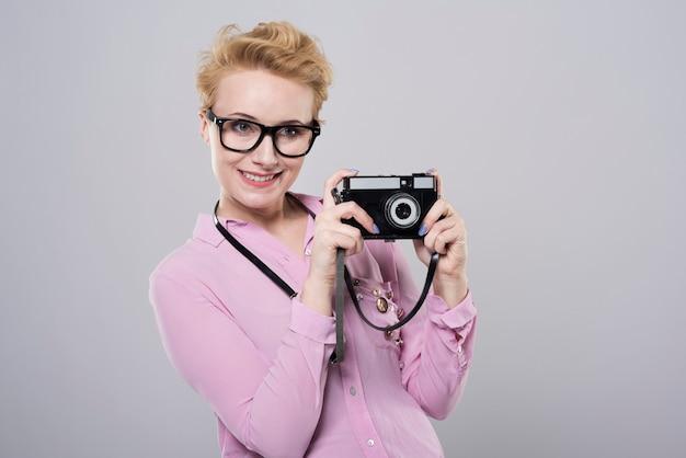 Mulher tirando fotos com câmera retro