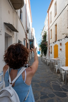 Mulher tirando fotos com seu smartphone em uma bonita vila costeira