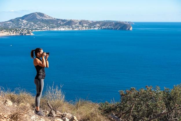 Mulher tirando fotos com sua câmera para a paisagem, na natureza do peñon de ifach em calpe