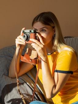 Mulher tirando fotos com uma câmera fotográfica retrô