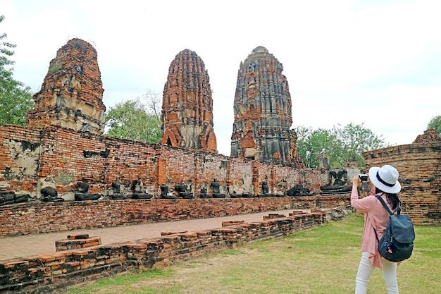 Mulher tirando fotos de estupas e ruínas de imagens de buda no templo wat mahathat ayutthaya, tailândia