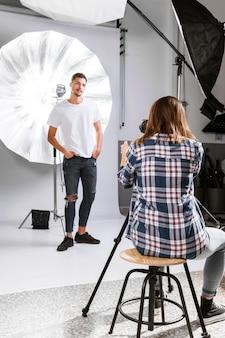 Mulher tirando fotos de homem bonito em estúdio