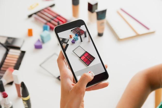 Mulher tirando fotos de produtos de maquiagem