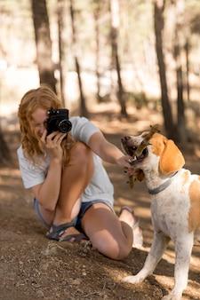 Mulher tirando fotos de seu cachorro de longa distância