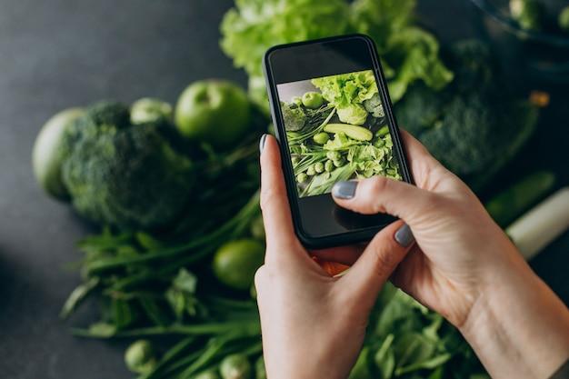 Mulher tirando fotos de vegetais verdes na mesa
