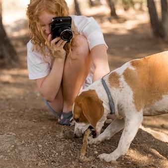 Mulher tirando fotos do cachorro mordendo uma tora
