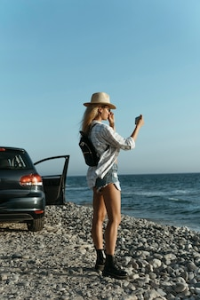 Mulher tirando fotos do mar de carro