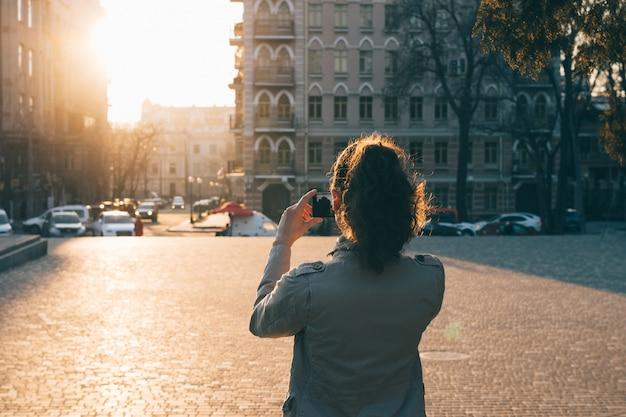 Mulher tirando fotos em um telefone inteligente em uma cidade velha ao pôr do sol