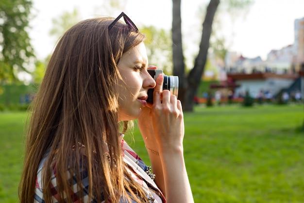 Mulher tirando fotos na câmera ao pôr do sol