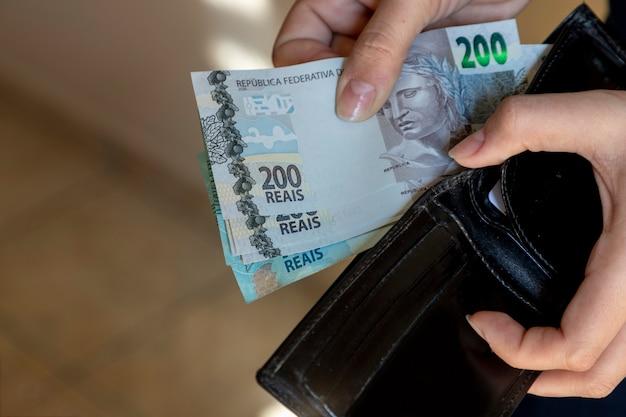 Mulher tirando notas de dinheiro brasileiras da carteira.