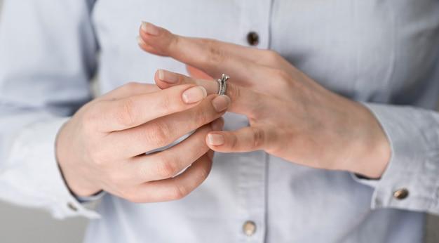 Mulher tirando o anel de casamento