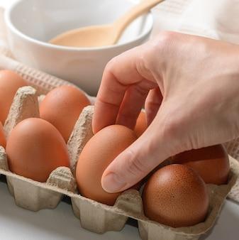 Mulher tirando ovo cru da embalagem