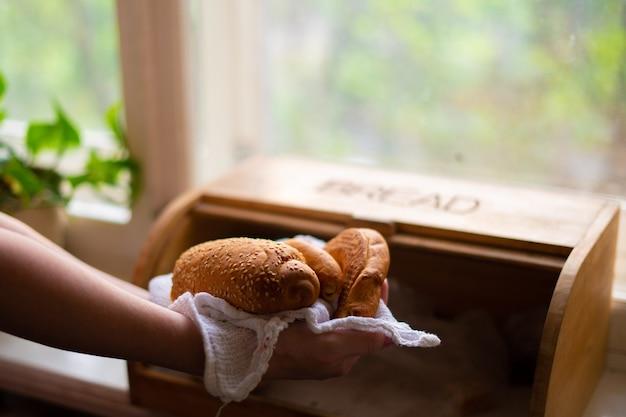 Mulher tirando pão de uma caixa de pão na cozinha de casa