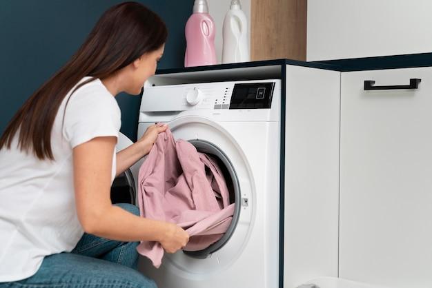 Mulher tirando roupas da máquina de lavar