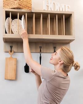 Mulher tirando um prato da prateleira