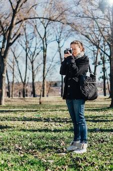 Mulher tirando uma foto com a câmera analógica antiga
