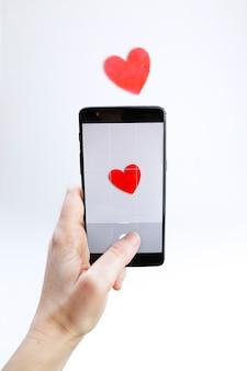 Mulher tirando uma foto com seu smartphone de um coração de madeira vermelho
