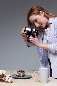 Mulher tirando uma foto de comida com câmera profissional