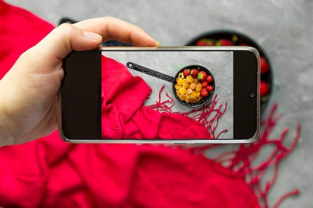Mulher tirando uma foto de comida na moda - cereal panqueca com smartphone