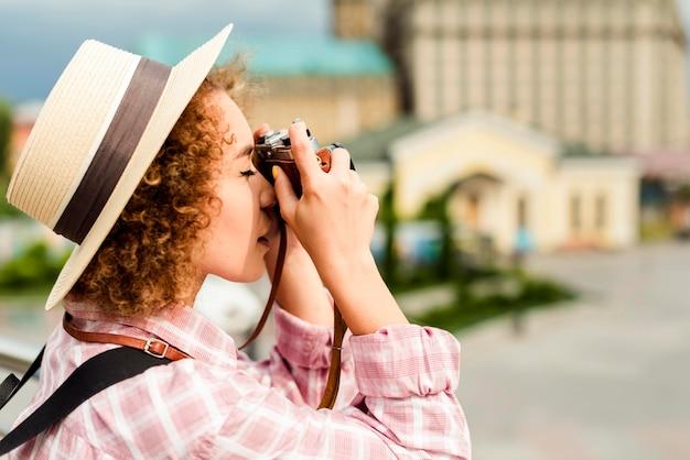 Mulher tirando uma foto de lado com uma câmera