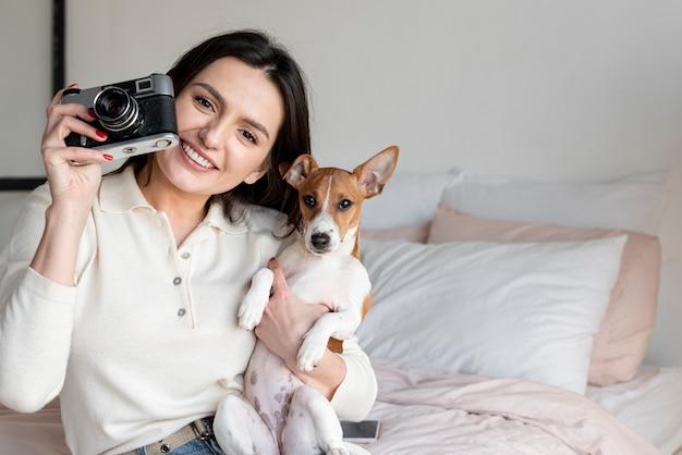 Mulher tirando uma foto enquanto segura o cachorro