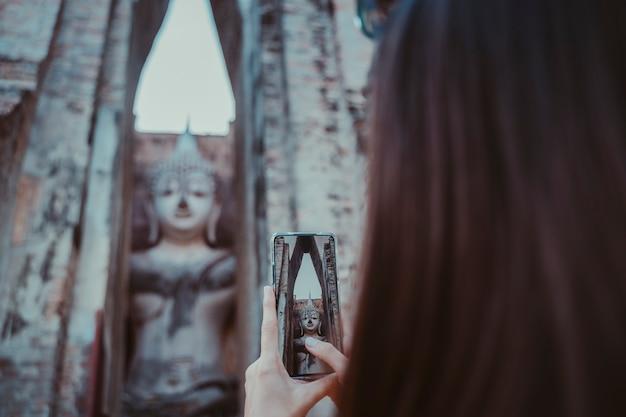 Mulher tirando uma foto horizontal com o telefone de tela em sentado buddha em wat mahathat no parque nacional de sukhothai.