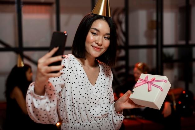 Mulher tirando uma selfie com um presente