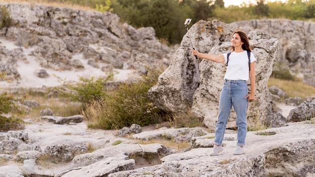 Mulher tirando uma selfie em um belo lugar novo com espaço de cópia