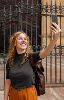 Mulher tirando uma selfie na frente do prédio