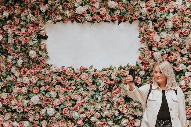 Mulher tirando uma selfie perto da flor na parede com espaço em branco