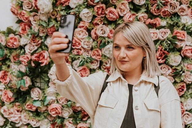 Mulher tirando uma selfie perto da instalação da parede de flores