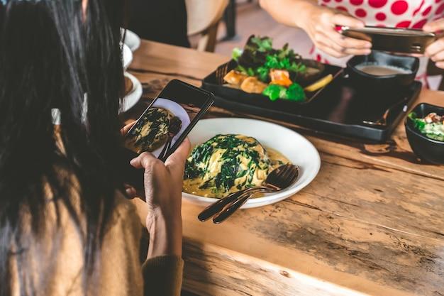 Mulher tirar uma foto com o celular antes de ter boa comida.