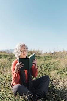 Mulher tiro cheio, lendo ao ar livre