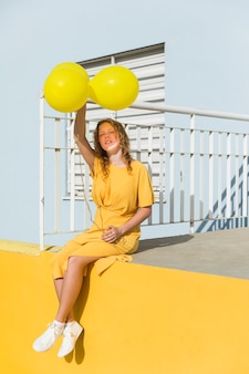 Mulher tiro cheio, segurando balões