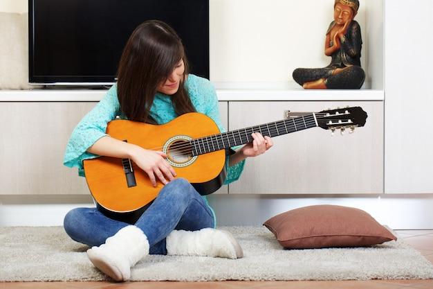 Mulher toca guitarra em casa