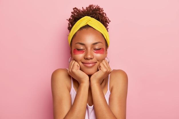 Mulher toca o queixo, usa adesivos de colágeno para inchar, reduz linhas finas, tem cabelo encaracolado, mantém os olhos fechados, mostra sua pele morena saudável, isolada em parede rosa