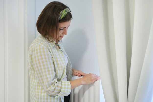 Mulher toca radiador de aquecimento no interior de casa