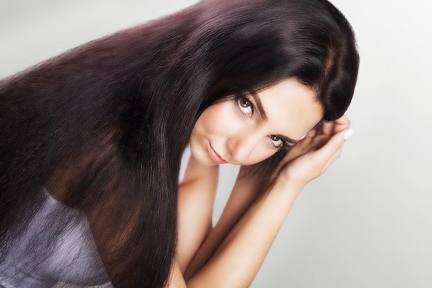 Mulher toca seu cabelo castanho longo e saudável.